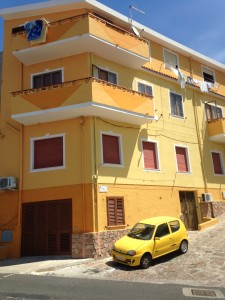 Groteske facadefarver i den nye del af Castelsardo by. Selv bilen er gul...